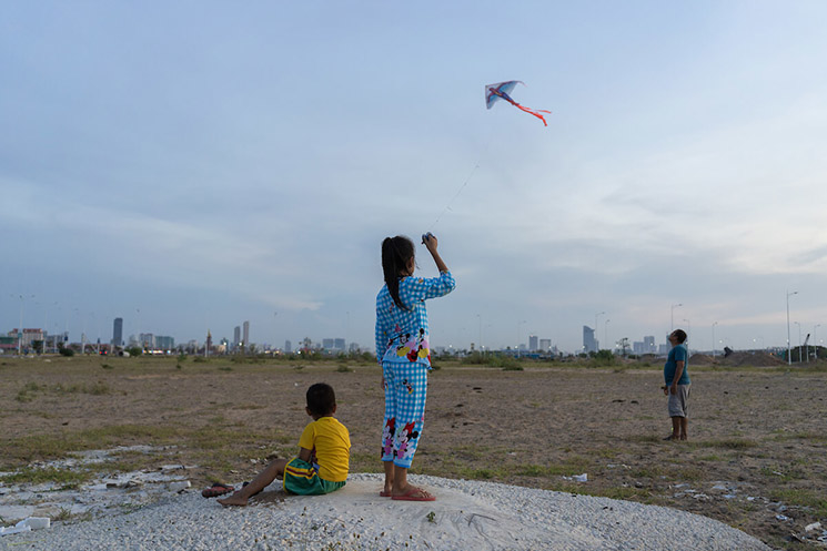 A girl plays with a kite on an area of wetland that has been filled